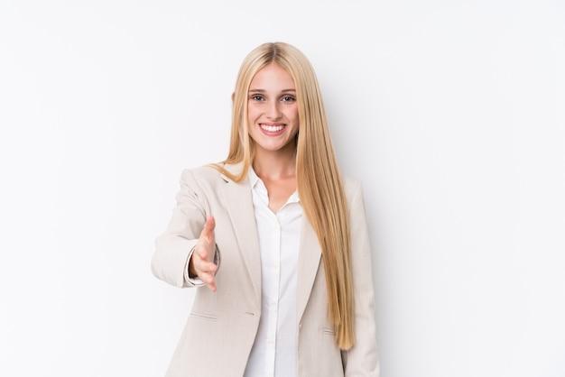 Jonge zakelijke blonde vrouw die zich uitstrekt hand vooraan in groetgebaar.