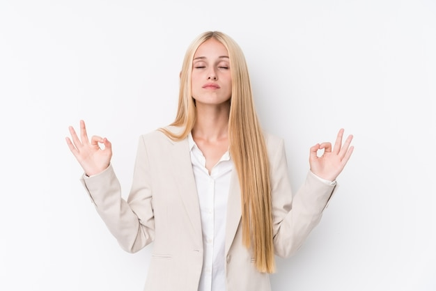 Jonge zakelijke blonde vrouw op witte achtergrond ontspant na een dag hard werken, ze presteert yoga.