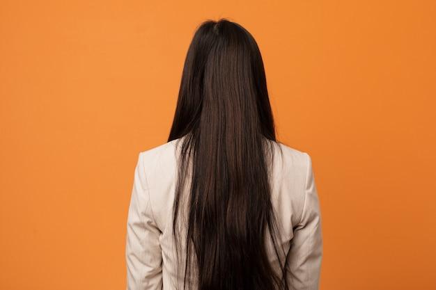Jonge zakelijke chinese vrouw van achteren, terugkijkend.