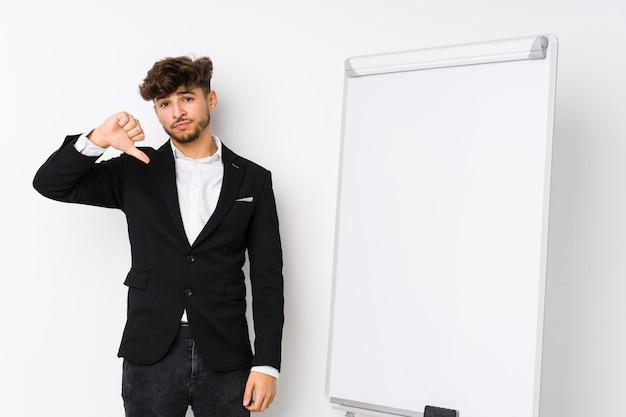 Jonge zakelijke coaching arabische man met een afkeer gebaar, duimen naar beneden. meningsverschil concept.