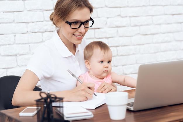 Jonge zakelijke dame probeert te werken met pasgeboren baby.