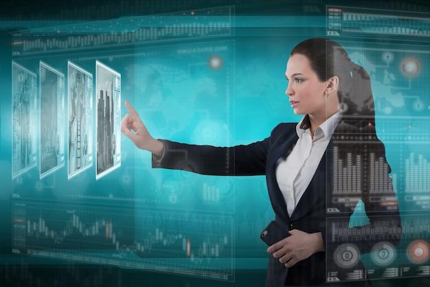 Jonge zakelijke dame werkt met virtuele grafische interface in futuristisch kantoor