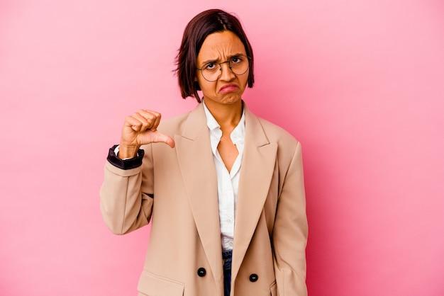 Jonge zakelijke gemengd ras vrouw geïsoleerd op roze achtergrond met een afkeer gebaar, duim omlaag. onenigheid begrip.