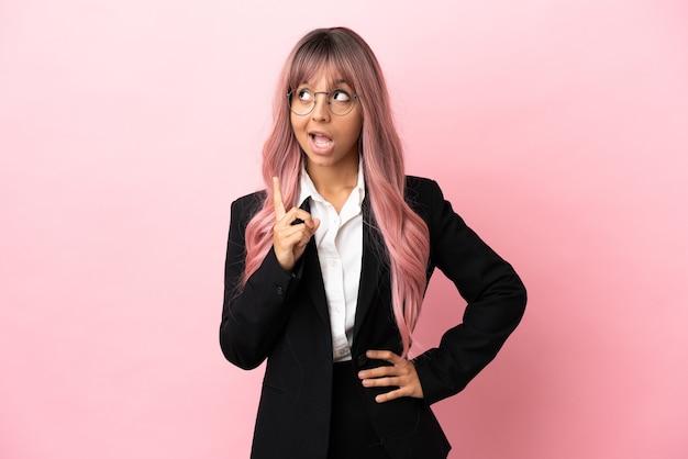 Jonge zakelijke gemengd ras vrouw met roze haar geïsoleerd op roze achtergrond denken een idee met de vinger omhoog