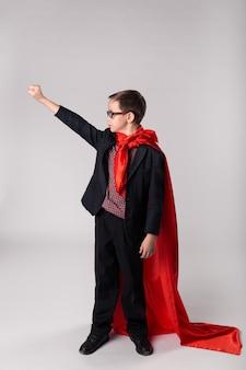 Jonge zakelijke jongen hand omhoog in superman cape