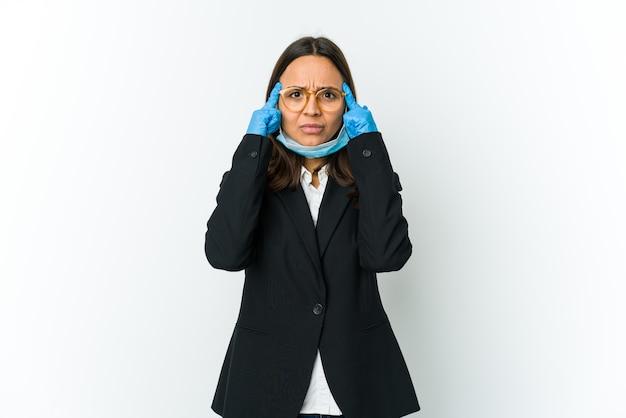 Jonge zakelijke latin vrouw die een masker draagt om te beschermen tegen covid geïsoleerd op een witte muur gericht op een taak, met wijsvingers wijzend hoofd
