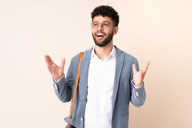 Jonge zakelijke marokkaanse man geïsoleerd op beige achtergrond met verrassende gezichtsuitdrukking