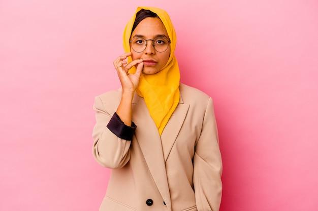 Jonge zakelijke moslimvrouw die op roze achtergrond met vingers op lippen wordt geïsoleerd die een geheim houden.