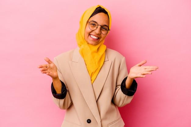 Jonge zakelijke moslimvrouw die op roze muur wordt geïsoleerd voelt zich zelfverzekerd door een knuffel te geven