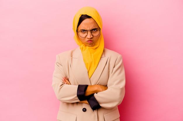 Jonge zakelijke moslimvrouw geïsoleerd op roze achtergrond fronsend gezicht in ongenoegen, houdt armen gevouwen.