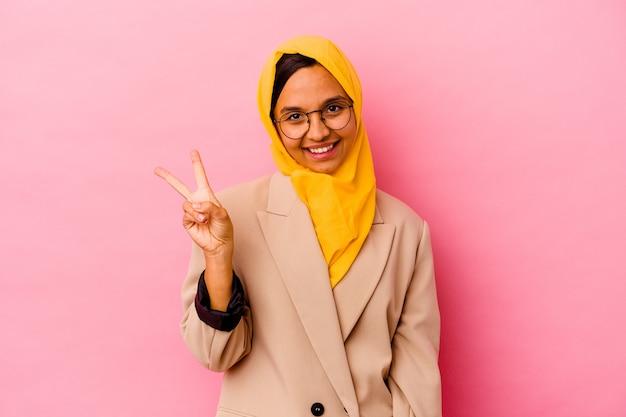Jonge zakelijke moslimvrouw geïsoleerd op roze muur blij en zorgeloos met een vredessymbool met vingers.
