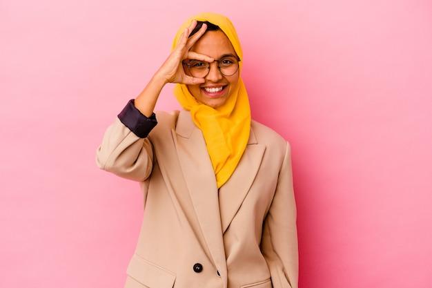 Jonge zakelijke moslimvrouw geïsoleerd op roze muur opgewonden houden ok gebaar op oog