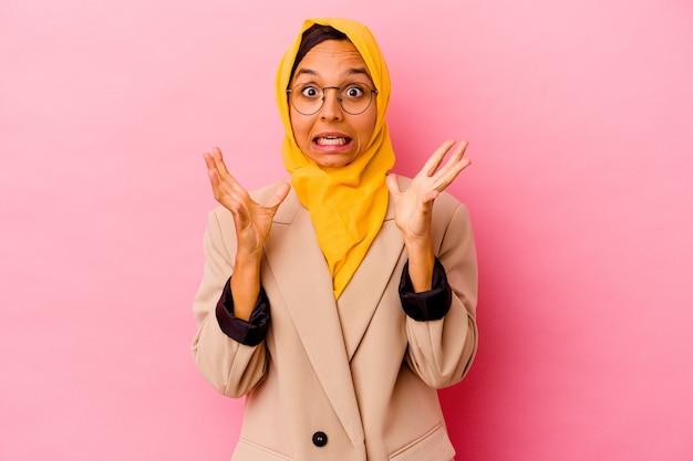 Jonge zakelijke moslimvrouw op roze viert een overwinning of succes, hij is verrast en geschokt.