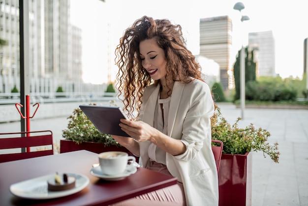 Jonge zakelijke roodharige vrouw op de tablet