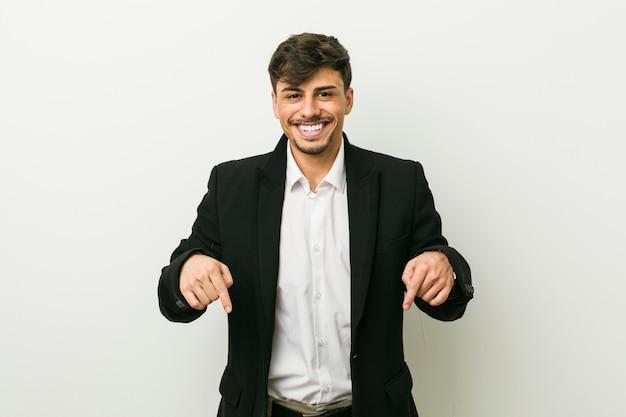 Jonge zakelijke spaanse man wijst naar beneden met vingers, positief gevoel.