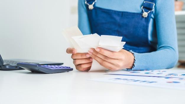 Jonge zakelijke vrouw berekening gezinsbudget, wat geld proberen te besparen met financiële papieren factuur.