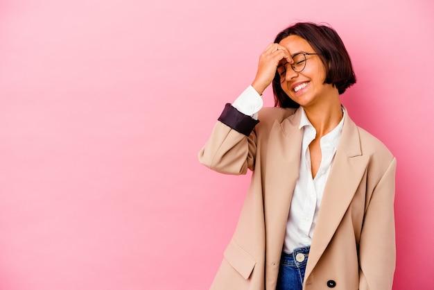 Jonge zakelijke vrouw van gemengd ras geïsoleerd op roze achtergrond lachen gelukkig, zorgeloos, natuurlijke emotie.