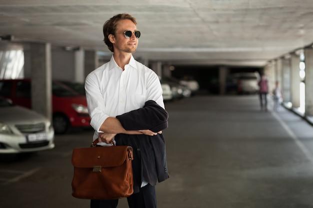 Jonge zakelijke werknemer in zonnebril staat op de parkeerplaats