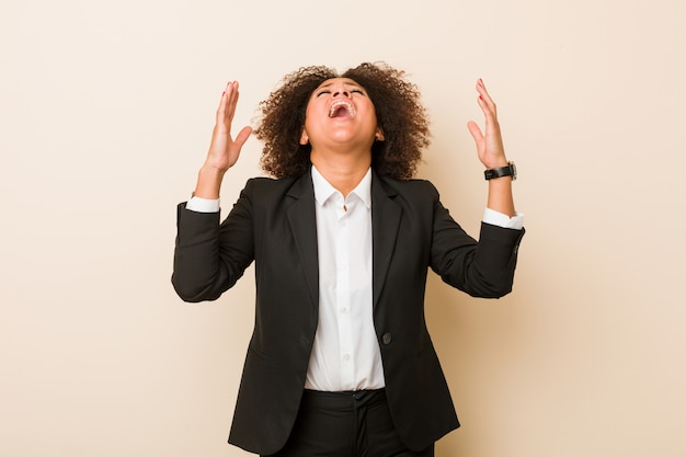 Jonge zaken afrikaanse amerikaanse vrouw die aan de hemel gilt, gefrustreerd omhoog kijkt.