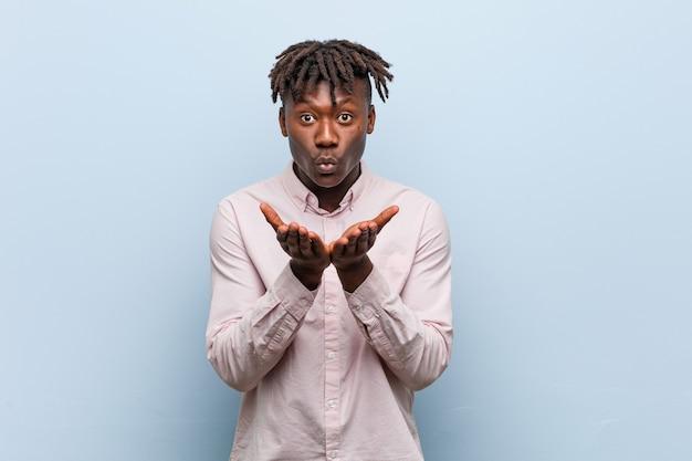 Jonge zaken afrikaanse zwarte man die lippen vouwt en palmen vasthoudt om luchtkus te sturen.