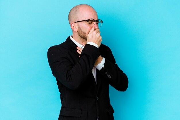 Jonge zaken blanke kale man geïsoleerd op blauwe muur lijdt aan keelpijn als gevolg van een virus of infectie