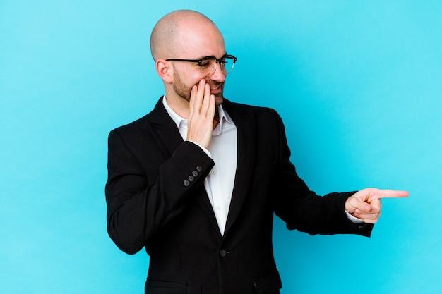Jonge zaken blanke kale man geïsoleerd op een blauwe muur zegt een roddel, wijzend naar de kant die iets meldt.