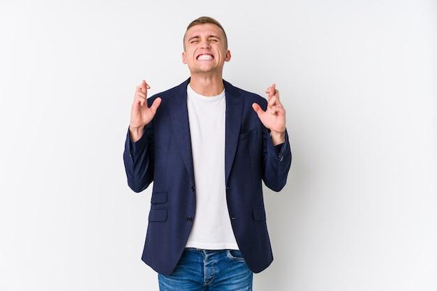 Jonge zaken blanke man kruising vingers voor geluk