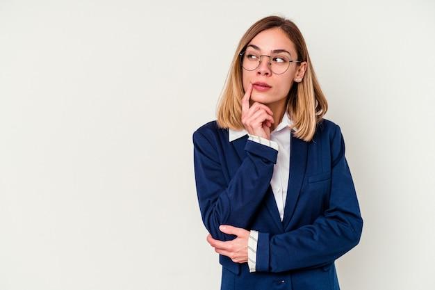 Jonge zaken blanke vrouw geïsoleerd op een witte muur opzij kijkt met twijfelachtige en sceptische uitdrukking