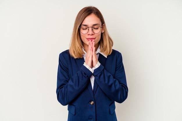 Jonge zaken blanke vrouw geïsoleerd op wit hand in hand bidden in de buurt van de mond, voelt zich zelfverzekerd.