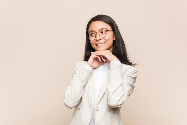 Jonge zaken chinese vrouw houdt handen onder de kin, kijkt gelukkig opzij.