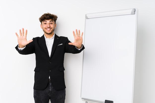 Jonge zaken die arabische mens trainen die nummer tien met handen toont.
