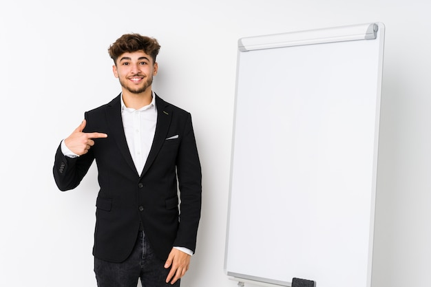 Jonge zaken die arabische mensenpersoon coachen die met de hand richten naar een ruimte van het overhemdsexemplaar, trots en zeker