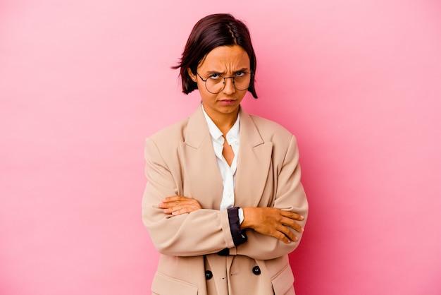 Jonge zaken gemengd ras vrouw geïsoleerd op roze achtergrond fronsend gezicht in ongenoegen, houdt armen gevouwen.