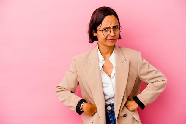 Jonge zaken gemengd ras vrouw geïsoleerd op roze muur fronsend gezicht in ongenoegen, houdt armen gevouwen.