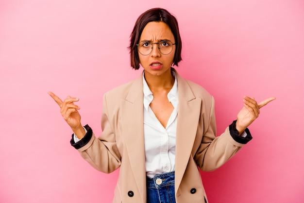 Jonge zaken gemengd ras vrouw geïsoleerd op roze muur wijzend naar verschillende kopie ruimtes, een van hen kiezen, tonen met vinger