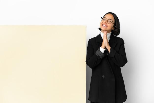 Jonge zaken gemengd ras vrouw met met een grote banner over geïsoleerde achtergrond houdt palm bij elkaar. persoon vraagt iets