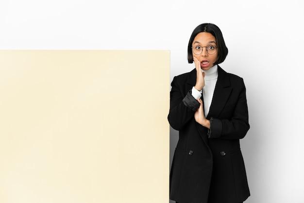 Jonge zaken gemengd ras vrouw met met een grote banner over geïsoleerde achtergrond met verbazing en geschokt gelaatsuitdrukking