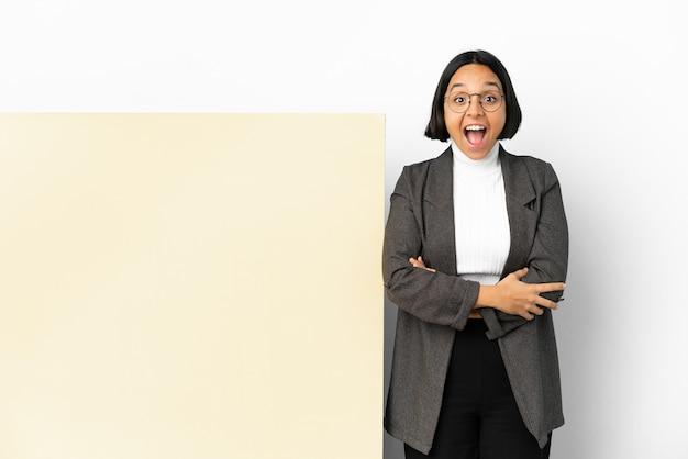 Jonge zaken gemengd ras vrouw met met een grote banner over geïsoleerde achtergrond met verrassingsgelaatsuitdrukking