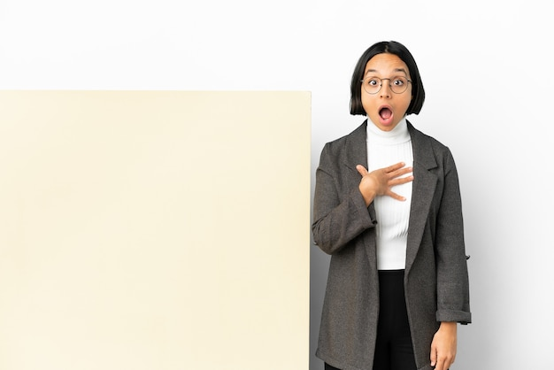 Jonge zaken gemengd ras vrouw met met een grote banner over geïsoleerde achtergrond verrast en geschokt terwijl ze naar rechts kijkt