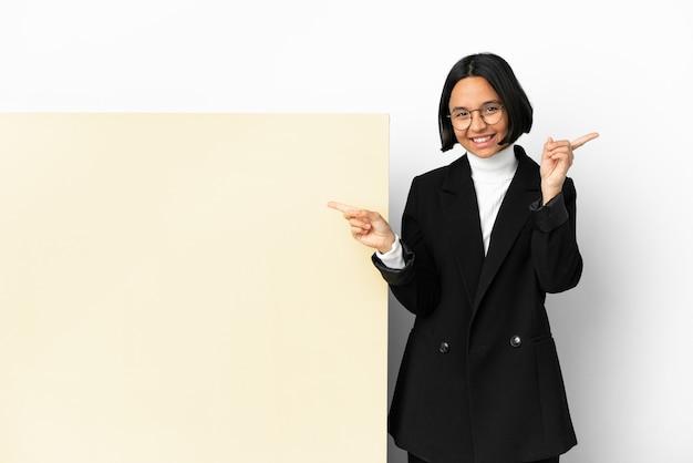 Jonge zaken gemengd ras vrouw met met een grote banner over geïsoleerde achtergrond wijzende vinger naar de zijtakken en gelukkig