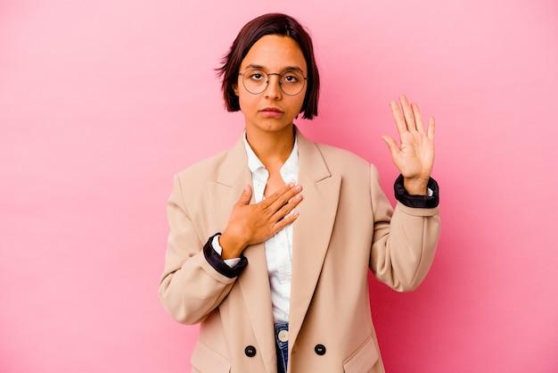 Jonge zaken gemengde rasvrouw die op roze muur wordt geïsoleerd die een eed aflegt, die hand op borst legt.