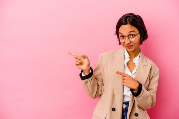 Jonge zaken gemengde rasvrouw die op roze muur wordt geïsoleerd die met wijsvingers naar een exemplaarruimte richt, opwinding en verlangen uitdrukt