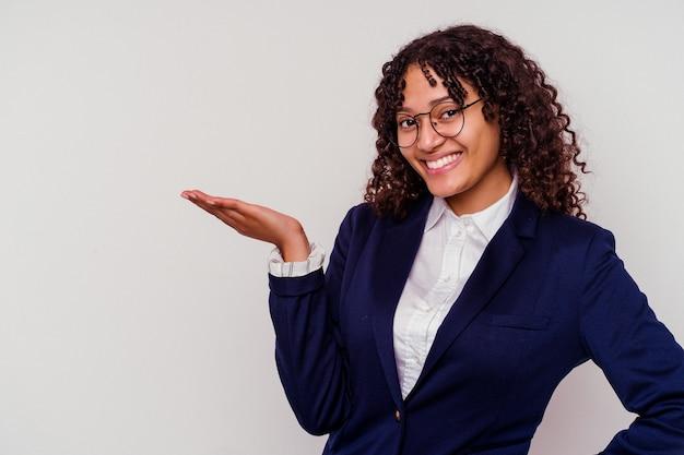 Jonge zaken gemengde rasvrouw die op witte achtergrond wordt geïsoleerd die een exemplaarruimte op een palm toont en een andere hand op taille houdt.