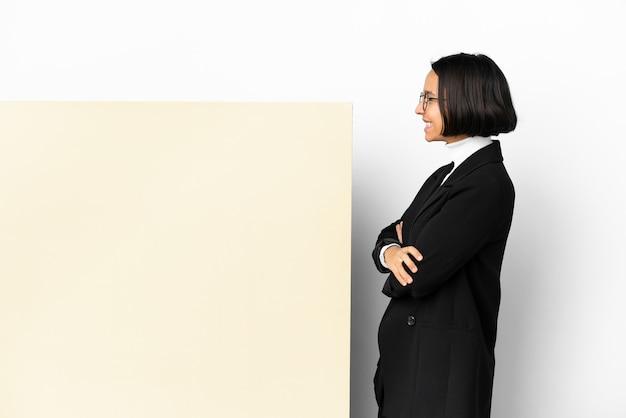 Jonge zaken gemengde rasvrouw met met een grote banner over geïsoleerde achtergrond in zijpositie