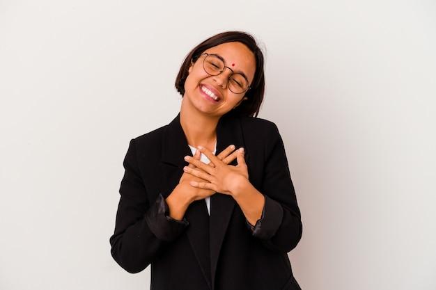 Jonge zaken indiase vrouw geïsoleerd op een witte achtergrond lachen houden handen op hart, concept van geluk.