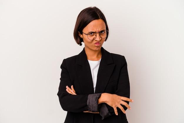 Jonge zaken indiase vrouw geïsoleerd op witte achtergrond fronsend gezicht in ongenoegen, houdt armen gevouwen.