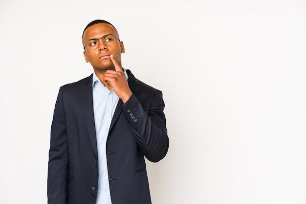 Jonge zaken latijns-man geïsoleerd op wit zijwaarts op zoek met twijfelachtige en sceptische uitdrukking.
