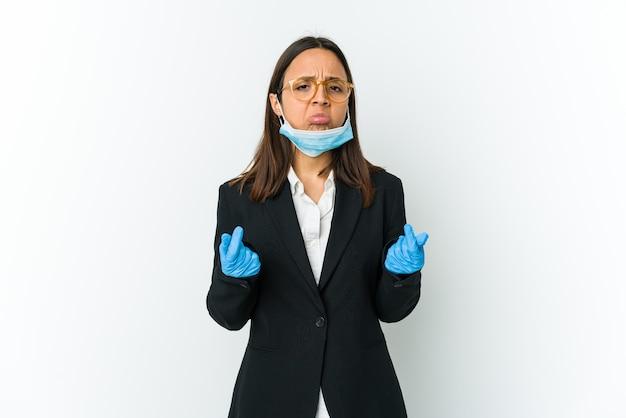 Jonge zaken latin vrouw draagt een masker om te beschermen tegen covid geïsoleerd op een witte muur waaruit blijkt dat ze geen geld heeft.