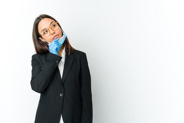 Jonge zaken latin vrouw draagt een masker om te beschermen tegen covid geïsoleerd op een witte muur zijwaarts kijken met twijfelachtige en sceptische uitdrukking.