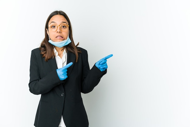 Jonge zaken latin vrouw draagt een masker om te beschermen tegen covid geïsoleerd op wit geschokt wijzend met wijsvingers naar een kopie ruimte.